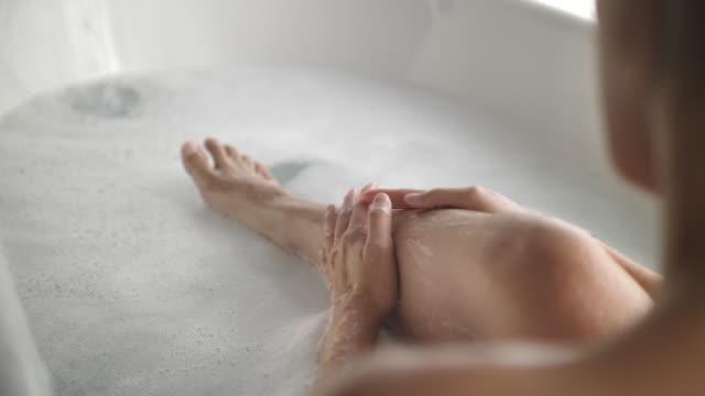 アジアの女性は、浴槽で彼女の足に入浴 - 体 洗う点の映像素材/bロール