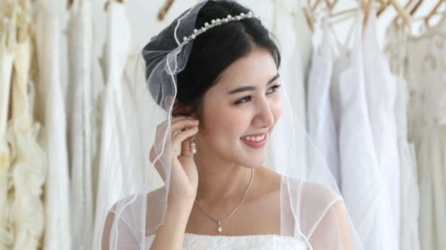 asian women beautiful bride put her jewelry and wedding earrings - prom fashion stock videos and b-roll footage