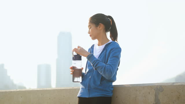 Asian women drink water and stand to rest after jogging a morning workout in the city. A city that lives healthy in the capital. Exercise, fitness, jogging, running, lifestyle, healthy concept.