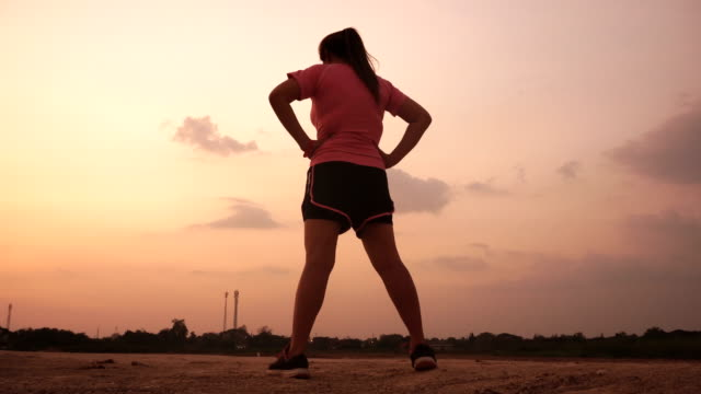 asian women jogging at sunset. - reggiseno sportivo video stock e b–roll