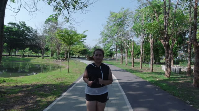 Video Asian women jogging in the street in the early morning sunlight in garden. concept of losing weight with exercise for health.