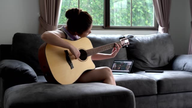 asian women learns to play the guitar with the help of an online tutorial - гитара стоковые видео и кадры b-roll