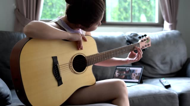 Asian women learns to play the guitar with the help of an online tutorial
