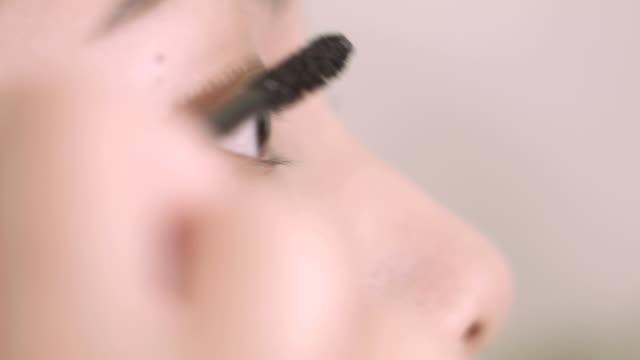 アジアの女性が彼女の自分でメイクアップ - 舞台化粧点の映像素材/bロール