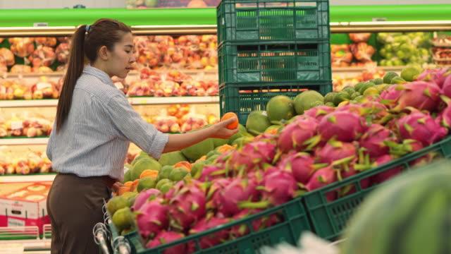 vídeos y material grabado en eventos de stock de mujeres asiáticas comprando verduras y frutas de comida saludable en supermercado - snack aisle