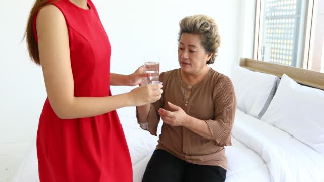 As mulheres asiáticas tomam o cuidado e que dão comprimidos ou medicina à mulher idosa para comer em casa - vídeo