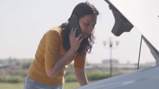 Asian women talking by phone with Car broken down on road opening the radiator bonnet Car and see engines