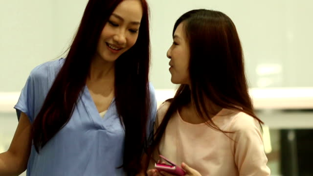 Asian women talking when taking escalator in shopping mall. video