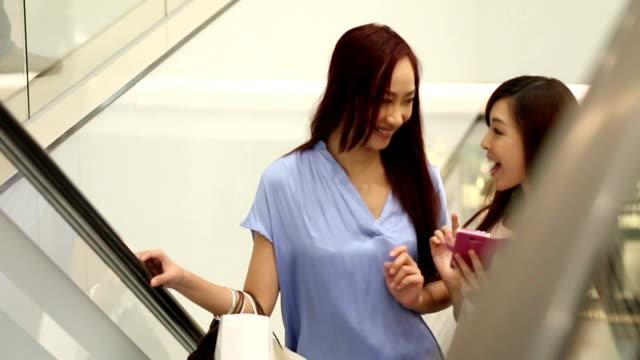 アジア女性に話す時で、ショッピングモールエスカレーターます。 - 小売り点の映像素材/bロール