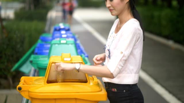 asian women throwing plastic bottle into the trash garbage - odzyskiwanie i przetwarzanie surowców wtórnych filmów i materiałów b-roll