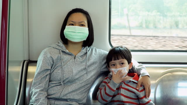 asian women with her son wear mask to protect germ during transportation by train. - face mask stock videos & royalty-free footage