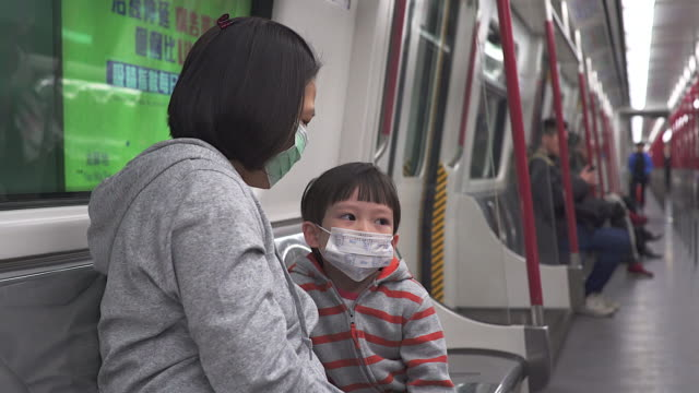 asian women with her son wear mask to protect germ during transportation by train. - mask filmów i materiałów b-roll