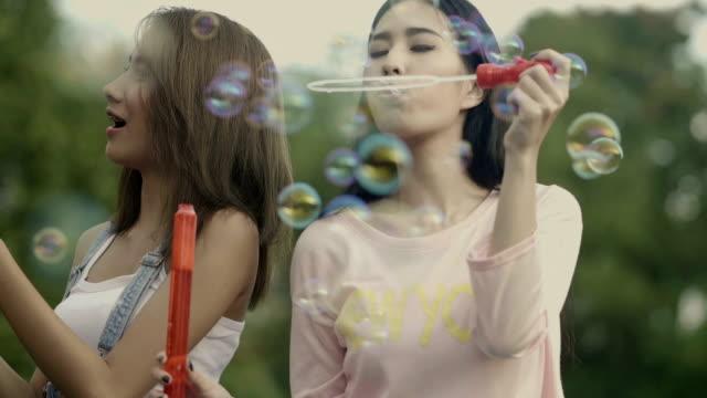 vídeos de stock e filmes b-roll de 2 asian womens blows bubbles - mulher balões