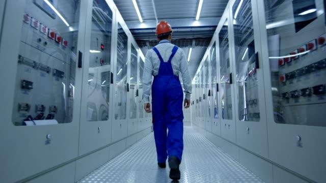 Asian worker walking in hallway of power station
