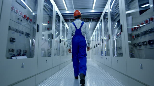 Asian worker walking in hallway of power station From below back view of Korean man in overall and hardhat walking in corridor with electrical equipment of solar power station power stock videos & royalty-free footage