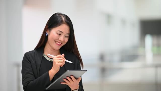 asiatische arbeitende frauen sind schön und niedlich, trägt einen schwarzen anzug, steht zuversichtlich mit einem tablet - weibliche angestellte stock-videos und b-roll-filmmaterial