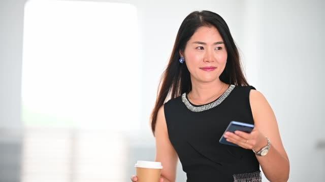 asiatische arbeitende frauen, schön und schön, trägt einen schwarzen anzug, steht zuversichtlich mit einem handy - weibliche angestellte stock-videos und b-roll-filmmaterial