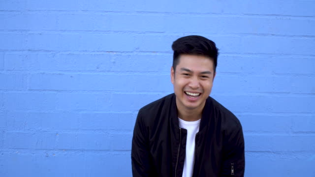 Asian Young Adult Hipster Chinese young man standing outdoors against building wall, laughing. blue background stock videos & royalty-free footage