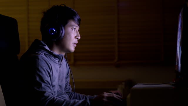 asiatische junge erwachsene mann online-spiele auf desktop-computer. - computerspieler stock-videos und b-roll-filmmaterial