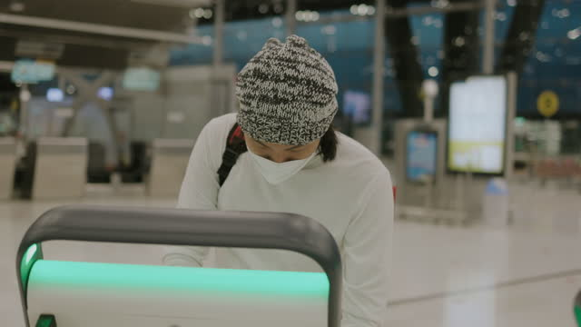 Asian young adult man with skullcap and protective face mask learn to using self-service check-in for the first time- stock video video