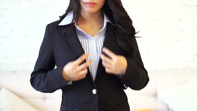 Asian young business woman putting on a suit video