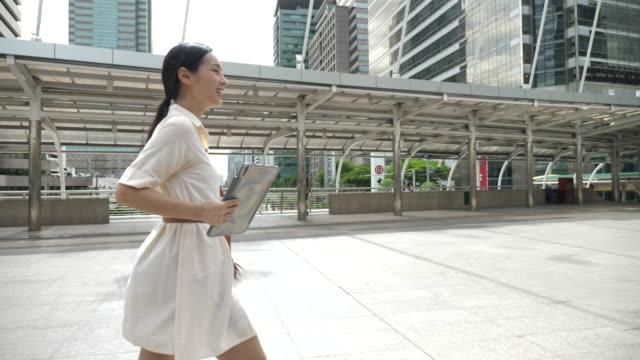 スローモーションアジアの若いビジネスウーマンウォーキング - 通勤点の映像素材/bロール