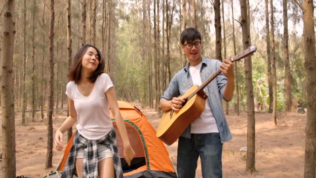 stockvideo's en b-roll-footage met aziatisch jong paar spel gitaar en zingend genietend van het kamperen in het pijnboombos - caravan