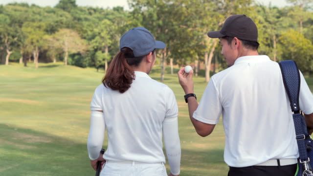 Asian young couples playing golf walking along fairway carrying golf bag.Success,Teamwork,Collaboration,Support,lifestyle,Togetherness.Confidence,Leadership,Power,Skill,Strength, Friendship,concept.Sports Cinemagraphs.Personal Trainer
