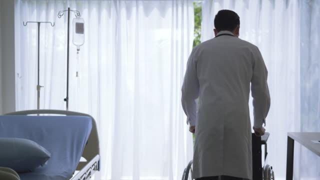 vídeos de stock, filmes e b-roll de jovens asiáticos doutor apoio paciente idoso, doctor consultoria e examinar a saúde do paciente mulher em saúde médico hospitalar ou escritório - pré estreia