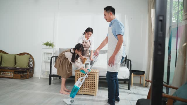 Asian young family teaching their daughter to clean living room. The kid and parents dancing and smiling together with fun. Happy moment of lovely family when cleaning the house with happiness.