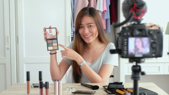 asian young female blogger recording vlog video with makeup cosmetic at home online influencer on social media concept.live streaming viral - influencer filmów i materiałów b-roll