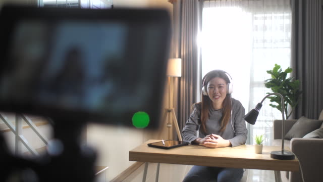 Asian young female blogger recording Vlog video with Talking to camera at home online influencer on social media