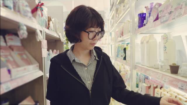 vídeos y material grabado en eventos de stock de chica joven asiática selecciona el elemento en los estantes de la tienda - eventos de etiqueta