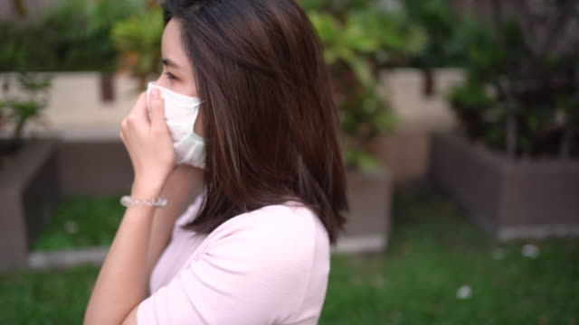 4K Asian young lady talking on the phone wearing white mask, coughing and sneezing, air pollution, virus covid19, respiratory disease, outside resident building, smart life self quarantine, order food