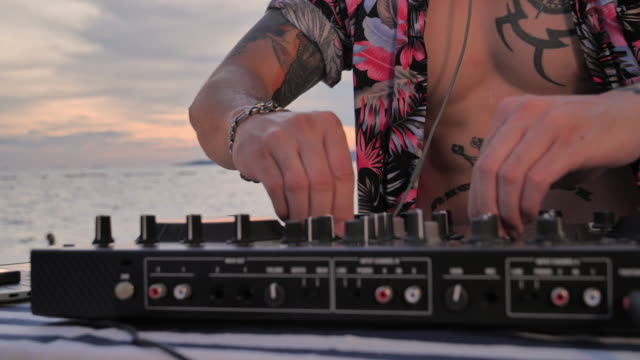 Asian young man DJ playing music on a turntable silhouette at the beach. Asian young man DJ playing music on a turntable silhouette at the beach. beach party stock videos & royalty-free footage