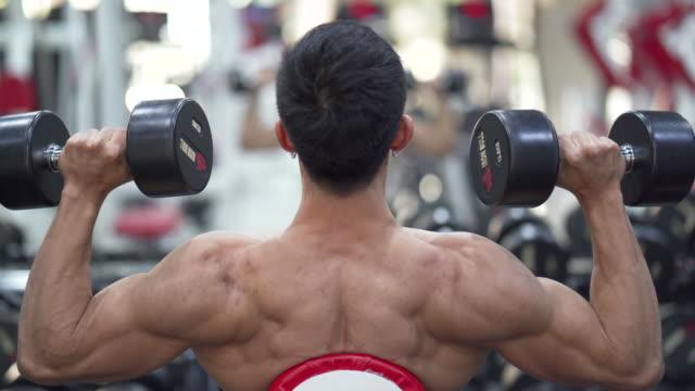 vídeos de stock e filmes b-roll de asian young man doing exercises in gym for arms and shoulder back view. - sistema cardiovascular