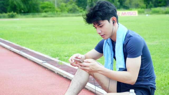 Asian young man relaxing holding smart phone play app
