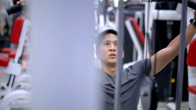 slo mo asian young man training on gym equipment. - sprzęt do ćwiczeń filmów i materiałów b-roll
