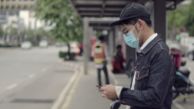 asian young man using smartphone in the city and wearing face mask for protection air pollution, partikel yarticulates and for protection grippe virus, influenza, coronavirus - smartphone mit corona app stock-videos und b-roll-filmmaterial