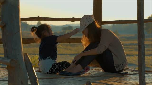 Asian young mother and her Daughter Playing in the hut on autumn field together video