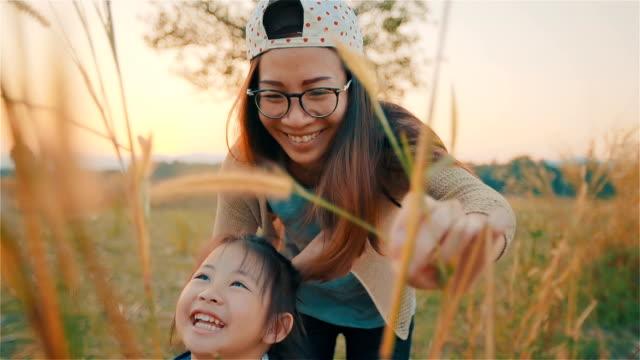 stockvideo's en b-roll-footage met aziatische jonge moeder en haar dochter spelen op de herfst veld samen - oost aziatische cultuur