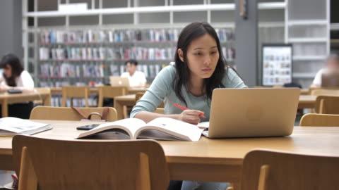 giovane studentessa asiatica in biblioteca che legge libri e prende appunti - imparare video stock e b–roll