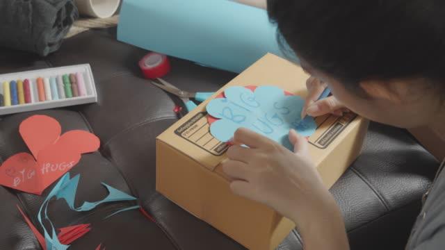 cu:亞洲年輕少女製作手工物品護理包。可愛的女孩包裝一個女孩盒準備送她的家人或朋友從遠處。 - 自製的 個影片檔及 b 捲影像
