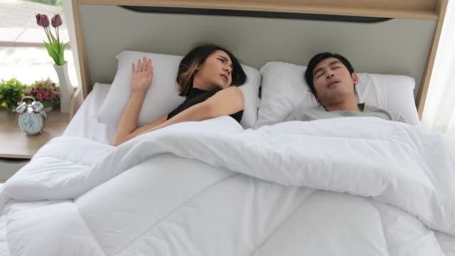 Asian young wife cannot sleep as her husband snoring beside her, woman closing ears with a pillow.