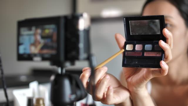 vídeos de stock, filmes e b-roll de asian jovem mulher blogger gravação vídeo vlog com maquiagem cosméticos em casa influenciador on-line no social media concept. live streaming viral - blogar