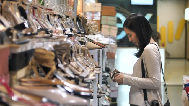 Asian Young woman choosing shoes at store Asian Young woman choosing shoes at store dress shoe stock videos & royalty-free footage