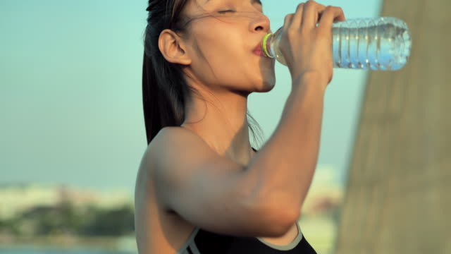 Asian young woman drinking water for hydrating after high intensity workout.Lifestyle,Success,Power,Healthy,Leadership,Women in Sport, Sport Prep - vídeo