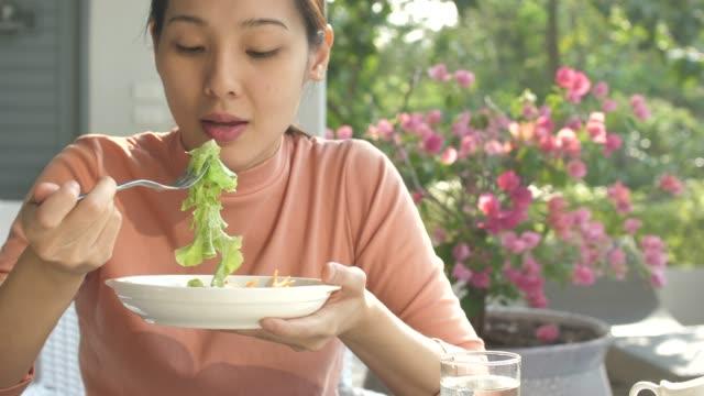 junge asiatin frischen salat essen - salat speisen stock-videos und b-roll-filmmaterial