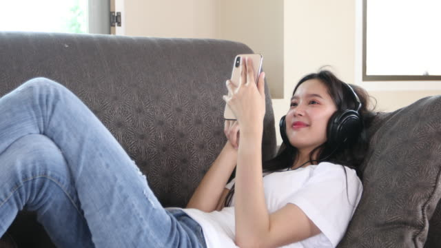 4K Asian young woman happy cheerful cute beautiful wears a headset for listening to music from a mobile phone and she is playing smartphone and lying on the sofa at home, the concept of a day of recreation and activities in the house.