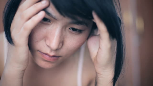 asian young woman holding head and feeling headache. - stress emotivo video stock e b–roll